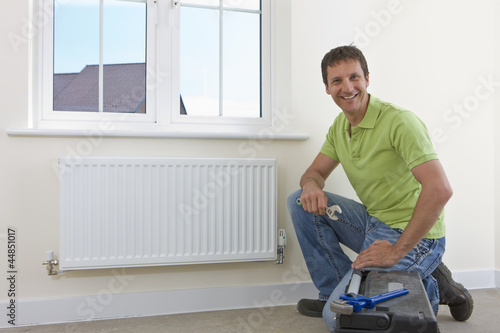 Portrait of smiling handyman fixing radiator