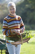 Portrait of smiling woman holding basket of fresh herbs in sunny garden