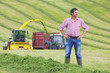 Portrait of confident farmer standing with hands on hips in field with tractors