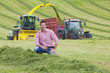 Portrait of farmer in hay field with tractors