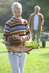 Portrait of smiling woman holding basket of fresh herbs and flowers in garden with man in background