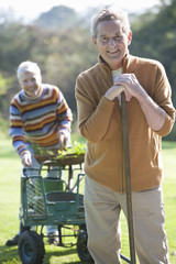 Portrait of smiling senior couple with gardening tools and cart