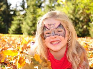 Lachendes Kind im Herbstlaub