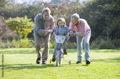 Smiling grandparents pushing granddaughter on bicycle with training wheels in yard