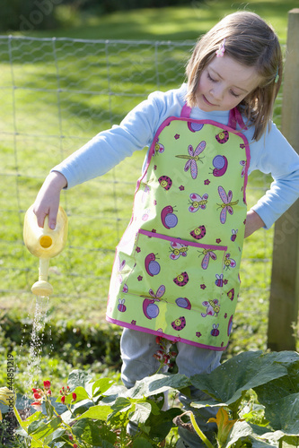 Girl in apron watering plants in garden with small watering can