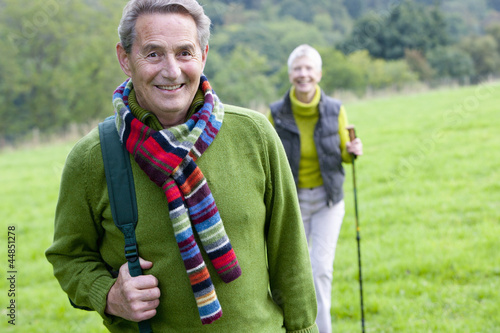 Portrait of smiling senior couple backpacking in field
