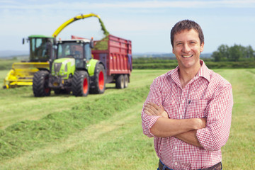 Portrait of smiling farmer with arms crossed in hay field with tractors