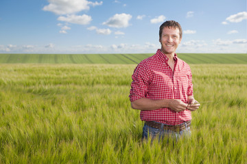 Portrait of smiling farmer in wheat field