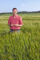 Portrait of smiling farmer standing in wheat field
