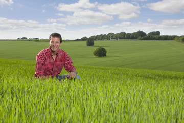 Portrait of smiling farmer in field