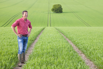 Portrait of smiling farmer with hands on hips in field