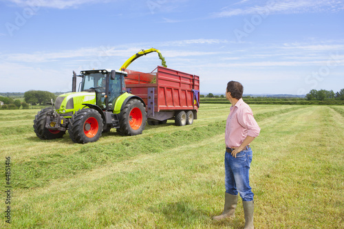 Farmer watching tractors harvest hay in field