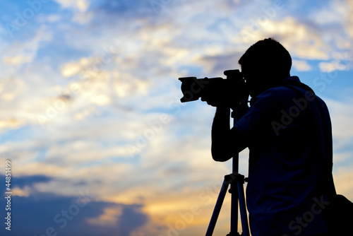Silhouette of a photographer taking a picture in sunset