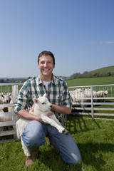 Portrait of smiling farmer holding lamb in pasture