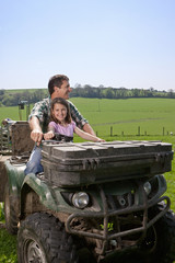 Farmer and daughter riding tractor in field