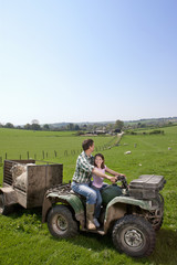 Shepherd and daughter riding tractor pulling trailer with sheep in field
