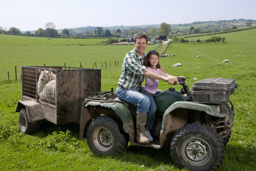 Portrait of shepherd and daughter riding tractor pulling trailer with sheep in field