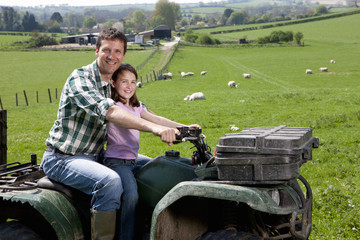 Portrait of shepherd and daughter riding tractor in field with sheep