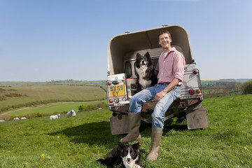 Portrait of shepherd with dog sitting on tailgate of truck