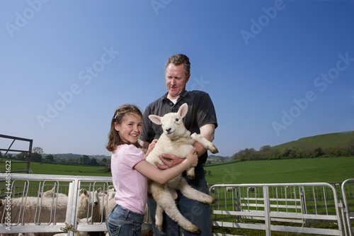 Shepherd and daughter holding lamb in pasture