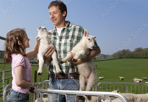 Shepherd and daughter holding lambs in pasture