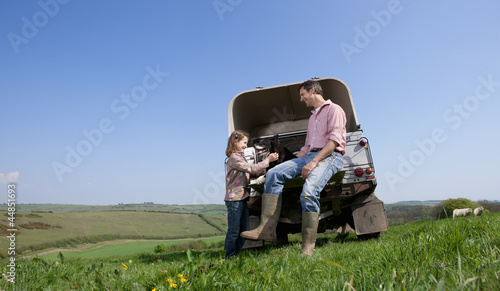 Farmer and daughter with dogs on tailgate of truck in field