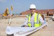 Portrait of smiling architect with blueprints at construction site