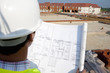 Close up of architect reviewing blueprints at construction site