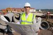 Portrait of architect holding blueprints at construction site