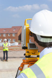Close up of surveyor looking towards co-worker through theodolite at construction site