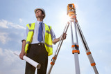 Sun shining behind surveyor with blueprint and theodolite