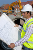 Architect reviewing blueprints at construction site