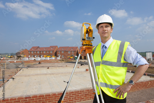 Portrait of confident surveyor with hands on hips next to theodolite at construction site