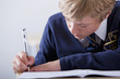 Close up of male student in school uniform taking exam at desk in classroom