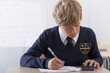 Male student in school uniform taking exam with calculator at desk in classroom
