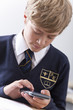 Close up of male student in school uniform using calculator