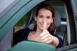 Attraktive junge Frau im Auto zeigt Daumen hoch