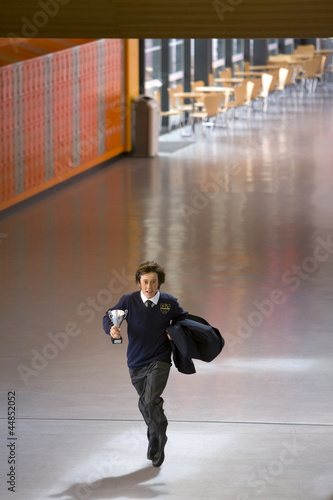 Male student in school uniform running with trophy in school corridor