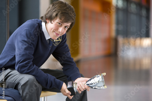 Portrait of smiling male student in school uniform holding trophy in school corridor