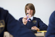 Portrait of male student in school uniform holding atom model at desk in classroom