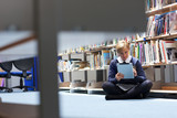 Female student in school uniform using digital tablet next to bookcase on library floor