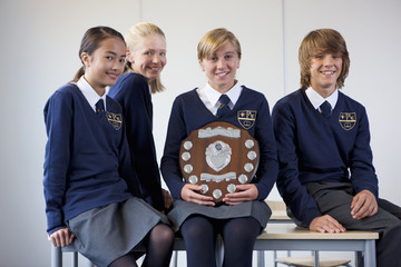 Portrait of smiling students in school uniforms holding award plaque