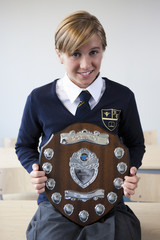 Portrait of smiling female student in school uniform holding award plaque