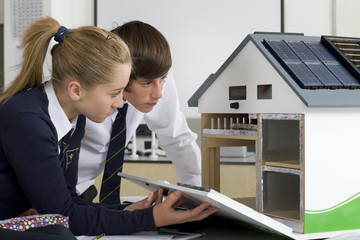 Students in school uniforms examining energy efficient house model in science class