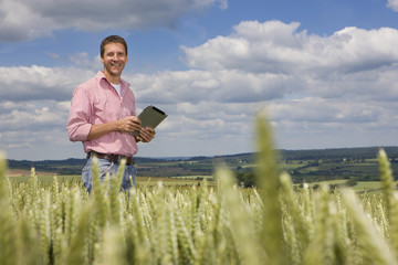 Portrait of smiling farmer holding digital tablet in sunny young wheat field