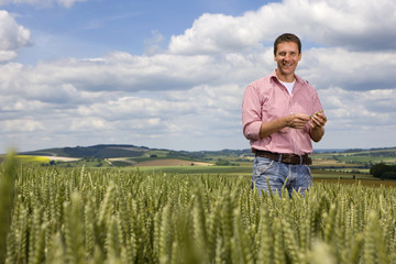 Portrait of smiling farmer standing in young wheat field