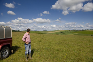 Farmer standing in sunny rural field with hands on hips