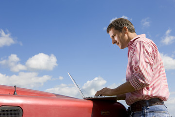 Farmer using laptop on truck