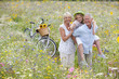 Senior couple standing in field of wildflowers carrying granddaughter