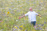 Senior man with arms outstretched enjoying field of wildflowers